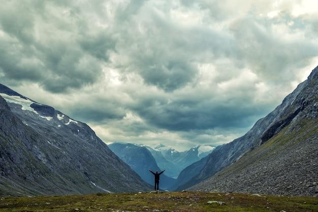 Het gelukkige mensengebaar van triomf met dient de lucht in. grappige wandelaar op de piek van zandsteenrots in nationaal park saksen zwitserland