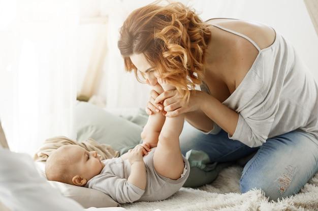 Het gelukkige moeder spelen met pasgeboren baby die kleine benen kust die de beste moedermomenten in gezellige slaapkamer doorbrengen. warme familiale sfeer. familie concept.