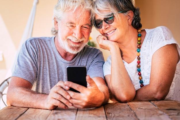 Het gelukkige mooie hogere oude paar doet een telefoongesprek met modern online technologieapparaat