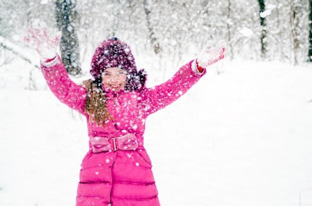 Het gelukkige mooie kindmeisje geniet buiten van sneeuw in de winter bospark. vrolijk meisje