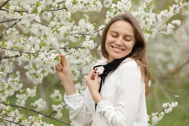 Het gelukkige mooie meisje deed haar medisch masker af om de geur van bloemen in te ademen. een meisje in een masker staat in bloesems. het einde van de quarantaine