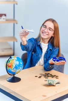 Het gelukkige mooie meisje kiest een vliegtuig als beter vervoer voor het reizen.