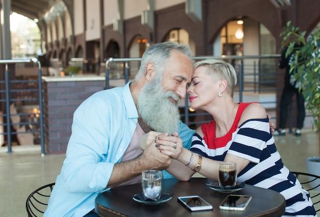 Het gelukkige mooie oudere paar drinkt samen koffie