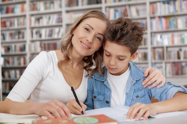 Het gelukkige mooie vrouw glimlachen, die haar zoon omhelst terwijl hij huiswerk doet