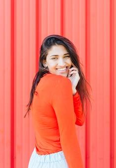 Het gelukkige mooie vrouw stellen voor rode achtergrond