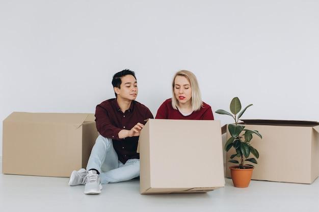 Het gelukkige multiculturele paar, de aziatische man en de kaukasische vrouw pakken dozen in nieuw huis uit. nieuwbouw woonhuis aankoop appartement concept.