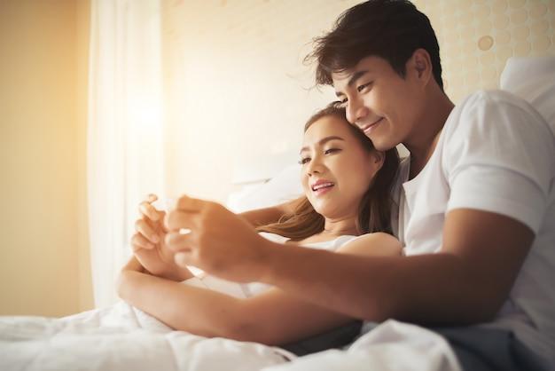 Het gelukkige paar die daarna glimlachen te weten komen positieve zwangerschapstest in slaapkamer