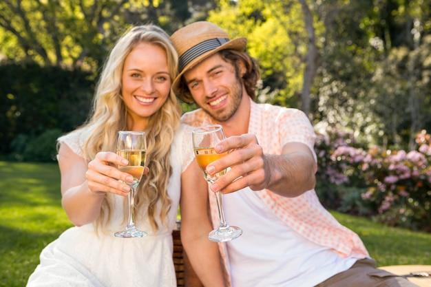 Het gelukkige paar die een picknick hebben en drinkt champagne in de tuin