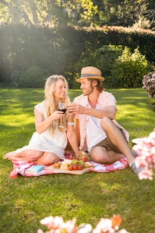 Het gelukkige paar die een picknick hebben en drinkt rode wijn in de tuin