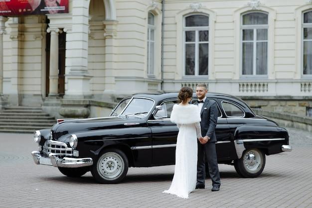 Het gelukkige paar die van het luxehuwelijk en dichtbij retro met boeketauto kussen omhelzen in de herfst