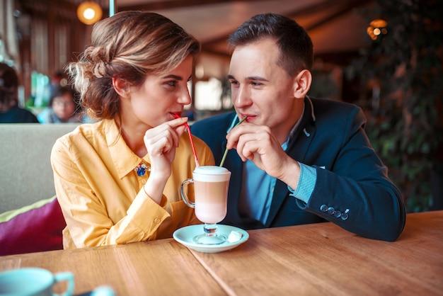 Het gelukkige paar drinkt samen een cocktail van de rietjes in restaurant. man en vrouw tijdens een romantisch diner