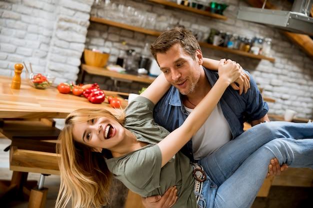 Het gelukkige paar geniet van elkaar in de moderne keuken terwijl man holdingsvrouw op handen