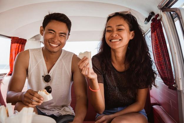 Het gelukkige paar glimlachen geniet van ontbijt binnen minivan