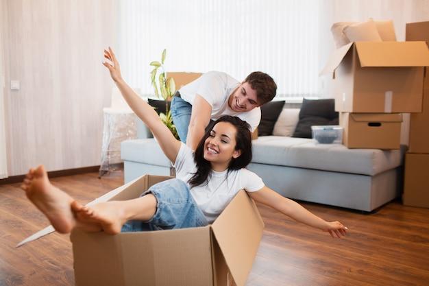 Het gelukkige paar heeft pret met kartondozen in nieuw huis bij bewegende dag