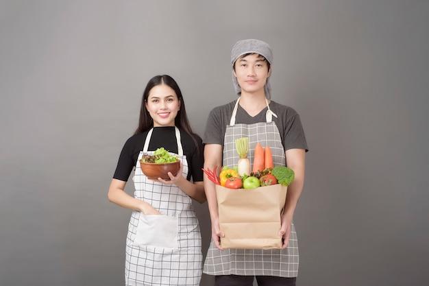 Het gelukkige paar houdt groenten in de grijze muur van de kruidenierswinkelzak