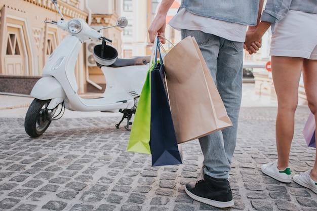Het gelukkige paar houdt het winkelen zakken in hand en geniet van