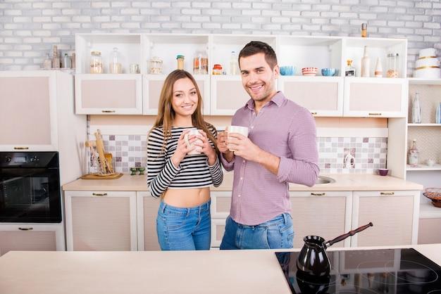 Het gelukkige paar in liefde drinkt koffie in de keuken