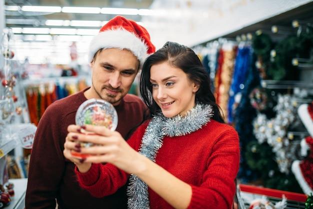 Het gelukkige paar kijkt op de bol van de kerstmissneeuw in supermarkt, familietraditie. winkelen in december van vakantiegoederen en decoraties