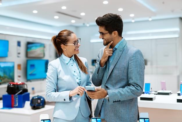 Het gelukkige paar kleedde zich in bedrijfskleren kiezend nieuwe slimme telefoon terwijl status in technologie-opslag.