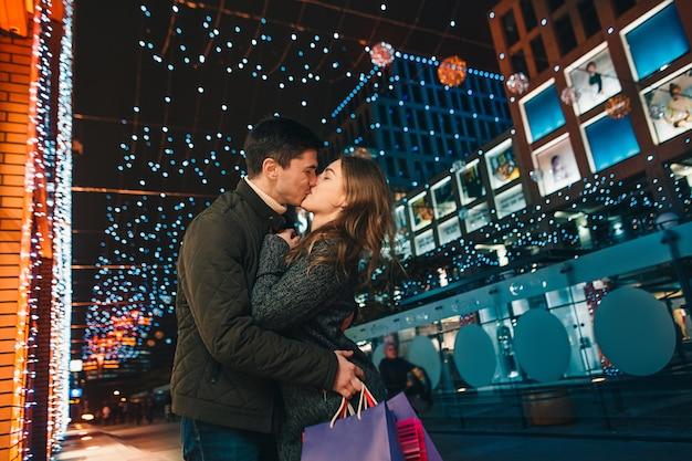 Het gelukkige paar met boodschappentassen die van de nacht genieten bij stadsachtergrond