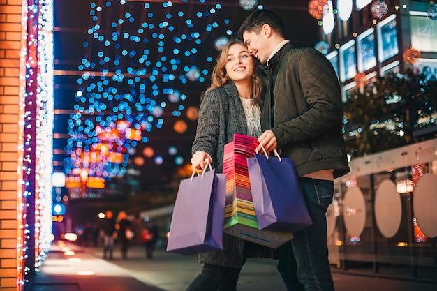 Het gelukkige paar met boodschappentassen genieten van de nacht in de stad