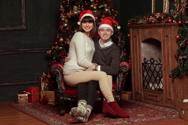 Het gelukkige paar stellen met santahoeden naast de kerstboom