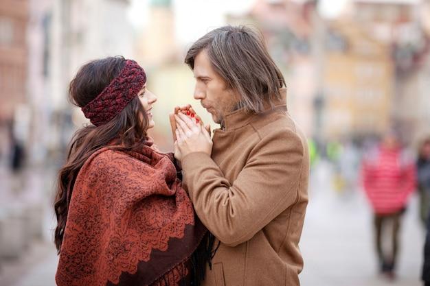 Het gelukkige paar stellen op het oude vierkant van de stad. vrij mooie vrouw en haar stijlvolle man knuffelen op straat. herfst of wintertijd.