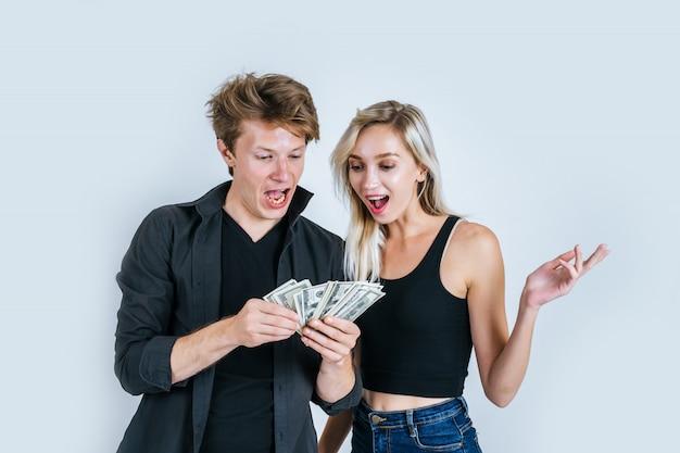 Het gelukkige paar toont dollarbankbiljet wat zaken maken