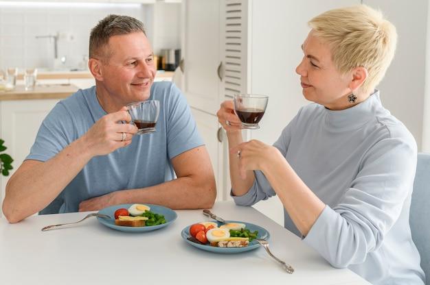 Het gelukkige paar van middelbare leeftijd geniet van het eten van gezond ontbijt dat samen naar elkaar kijkt