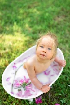 Het gelukkige peutermeisje neemt een melkbad met bloemblaadjes. klein meisje in een melkbad. boeketten van roze pioenrozen. baby baden. hygiëne en zorg voor jonge kinderen.