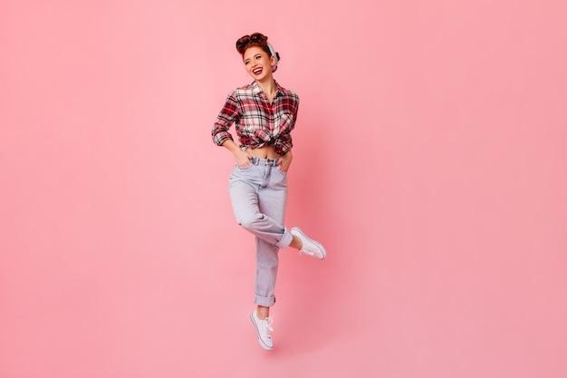 Het gelukkige pinupmeisje stellen met dient zakken in. lachende gember vrouw in geruit overhemd staande op roze ruimte.