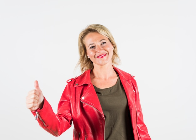 Het gelukkige portret van een rijpe vrouw die duim toont ondertekent omhoog tegen witte achtergrond