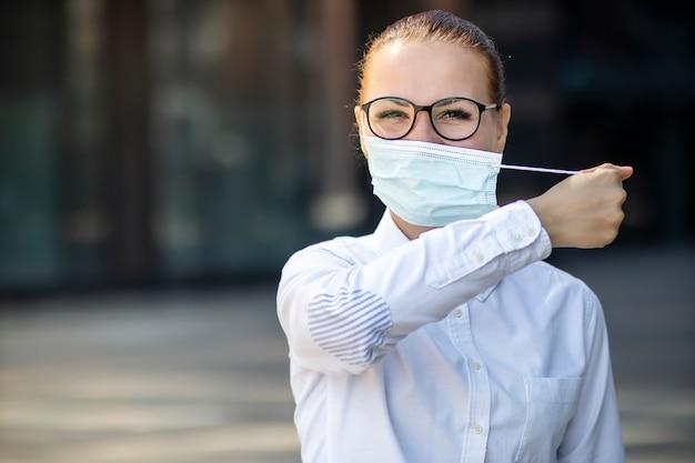 Het gelukkige positieve meisje, jonge mooie vrouw, onderneemster stijgt beschermend steriel medisch masker van gezicht in openlucht bedrijfsbureau, het glimlachen. gelukkig einde. overwinning op coronavirus. pandemic covid-19.