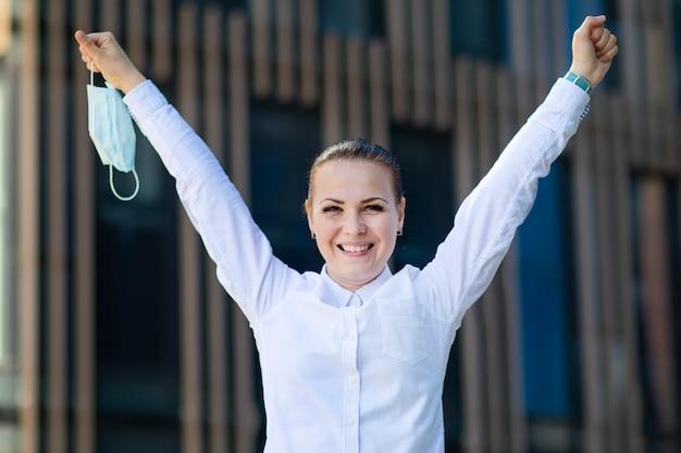 Het gelukkige positieve meisje, jonge mooie vrouw, onderneemster stijgt beschermend steriel medisch masker van gezicht met omhoog handen op, glimlachend. gelukkig einde. overwinning op coronavirus. pandemic covid-19, triumpth