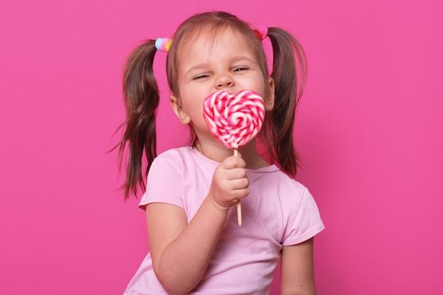 Het gelukkige speelse leuke meisje draagt roze t-shirt, staat geïsoleerd op roze, houdt heldere lolly in hand, etend het. gelukkig kind geniet van het doorbrengen van vrije tijd. jeugd en emoties concept.
