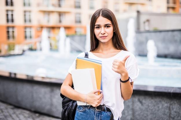 Het gelukkige studentenmeisje stellen met duimen die omhoog u in de straat bekijken