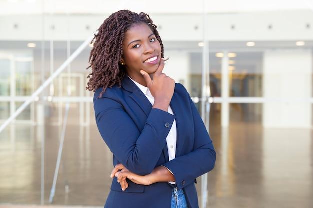 Het gelukkige succesvolle leider stellen dichtbij de bureaubouw