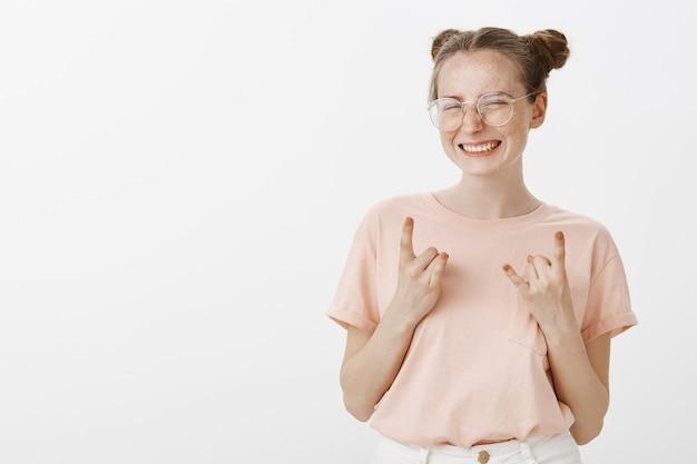 Het gelukkige succesvolle roodharige tienermeisje stellen tegen de witte muur