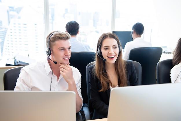 Het gelukkige telemarketingteam van bedrijfsmensen in call centrekantoor
