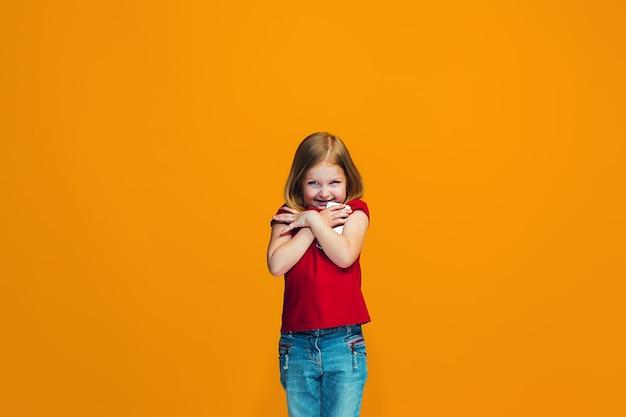 Het gelukkige tienermeisje dat en tegen oranje achtergrond bevindt zich glimlacht.
