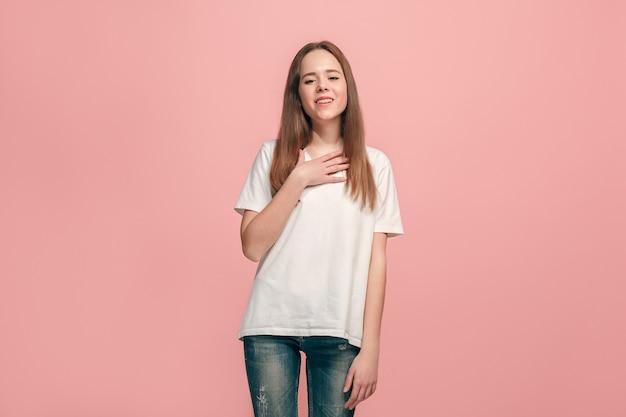 Het gelukkige tienermeisje dat en tegen roze muur bevindt zich glimlacht