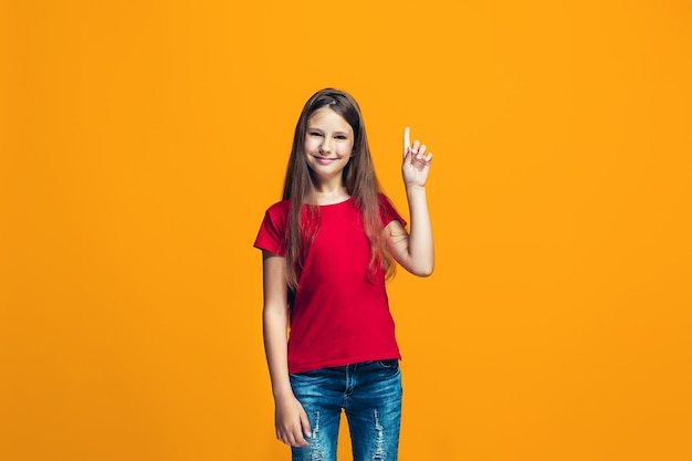 Het gelukkige tienermeisje dat en tegen sinaasappel bevindt zich glimlacht.