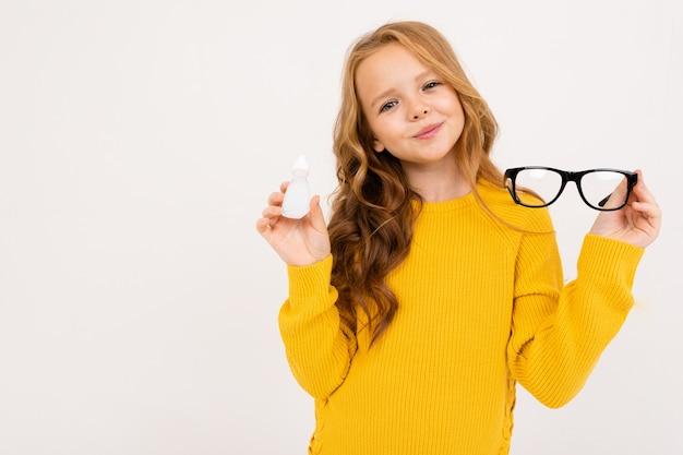 Het gelukkige tienermeisje met rood haar, hoody en gele broeken houdt contactlenzen en glazen die op wit worden geïsoleerd