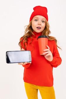 Het gelukkige tienermeisje met rood haar, rode hoed, hoody en gele broeken glimlacht, drinkt koffie en speelt telefoonspelen die op wit worden geïsoleerd