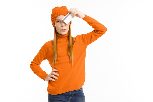 Het gelukkige tienermeisje met rood hoody haar, oranje en hoed houdt een creditcard die op witte achtergrond wordt geïsoleerd