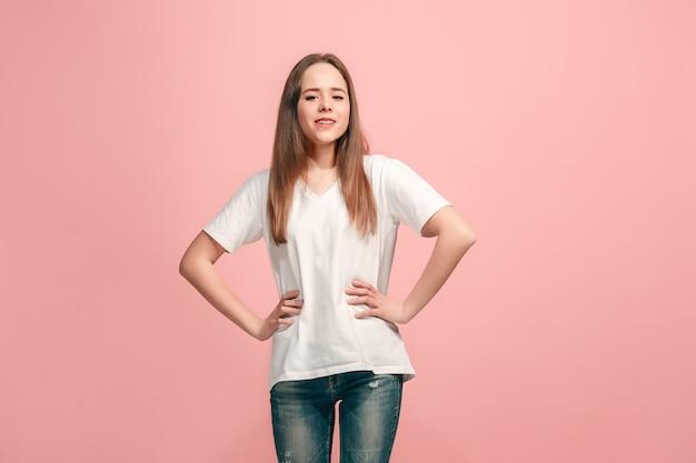 Het gelukkige tienermeisje staat en lacht tegen de roze muur
