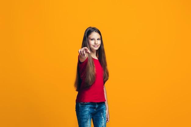 Het gelukkige tienermeisje wijst naar u, het portret van de halve lengteclose-up op oranje achtergrond.