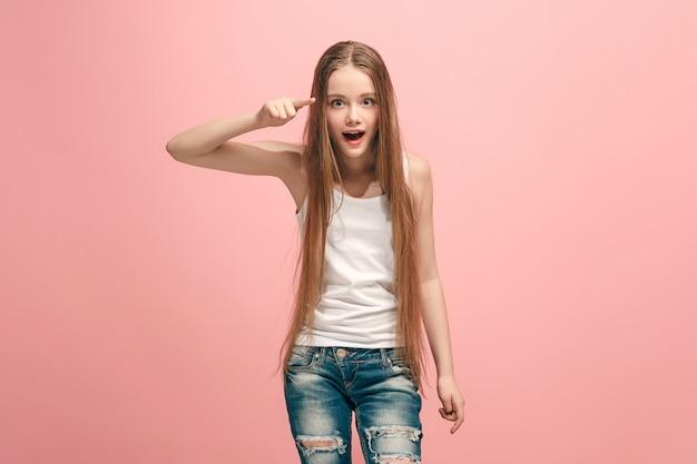 Het gelukkige tienermeisje wijst naar u, het portret van de halve lengteclose-up op roze.