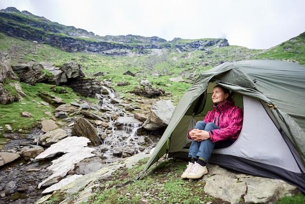 Het gelukkige toeristenwijfje zit in tent dichtbij bergstroom