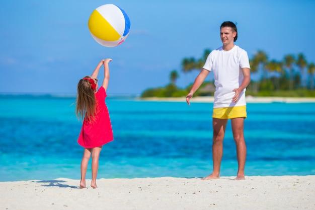 Het gelukkige vader en dochter spelen met bal die pret openlucht op strand hebben